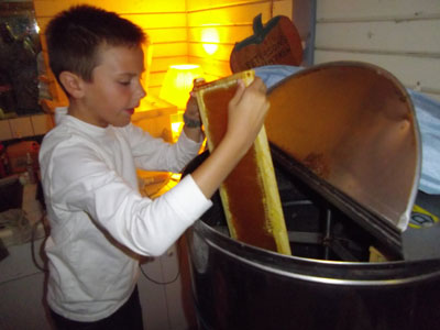 Blaine putting honey frame in the extractor
